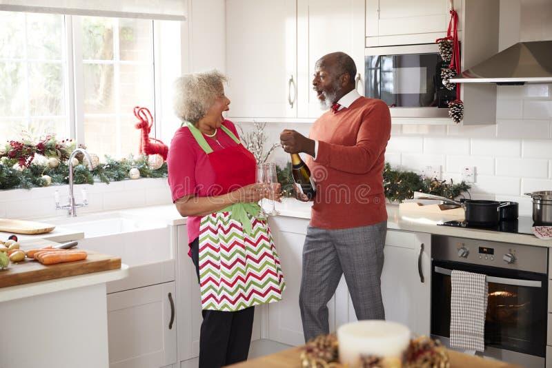 Hogere zwarte paar het openen champagne en het lachen samen in de keuken terwijl het voorbereiden van diner op Kerstmisdag, selec royalty-vrije stock fotografie