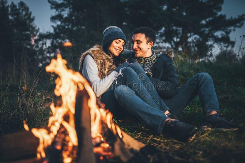 Hoguera cercana relajante de los pares bonitos en el bosque en la igualación de tim foto de archivo