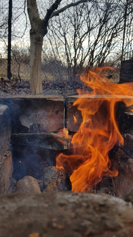 Hoguera con la llama anaranjada roja brillante en el brasero viejo del carbón de leña hecho de ladrillos ahumados quemados en la  fotografía de archivo