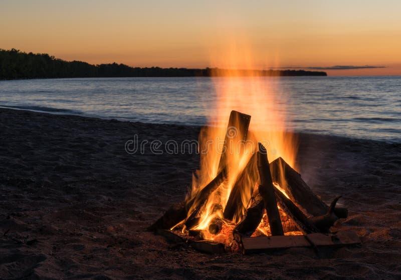 Hoguera de la playa en la puesta del sol imagenes de archivo