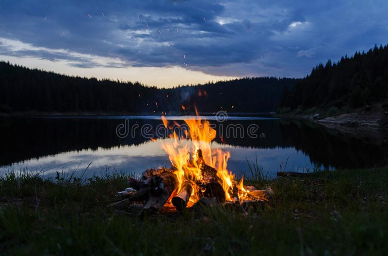 Hoguera después de la puesta del sol en las montañas al lado de un lago imágenes de archivo libres de regalías