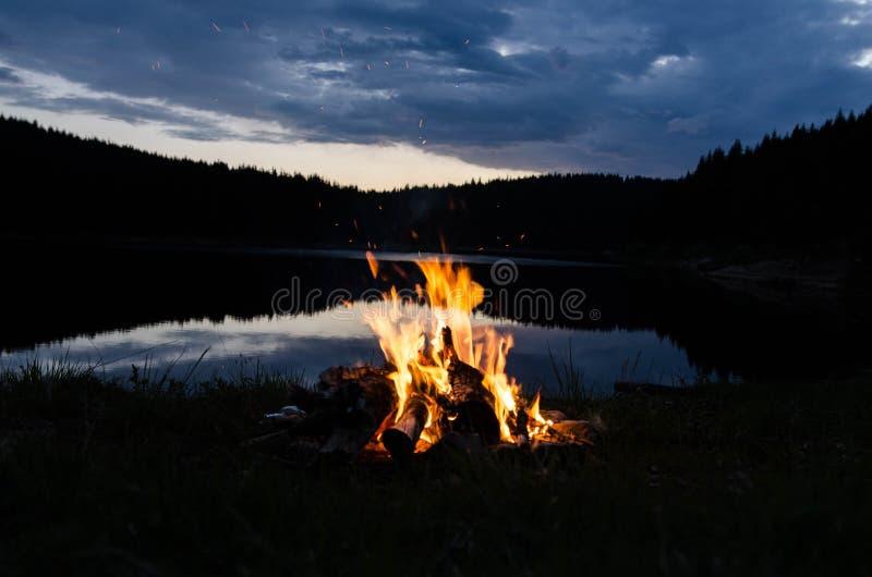 Hoguera después de la puesta del sol en las montañas al lado de un lago fotos de archivo libres de regalías