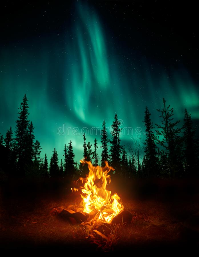 Hoguera en el desierto con la aurora boreal imagenes de archivo