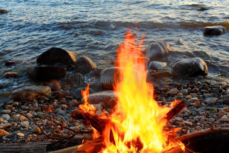 Hoguera en la orilla rocosa del lago fotografía de archivo libre de regalías