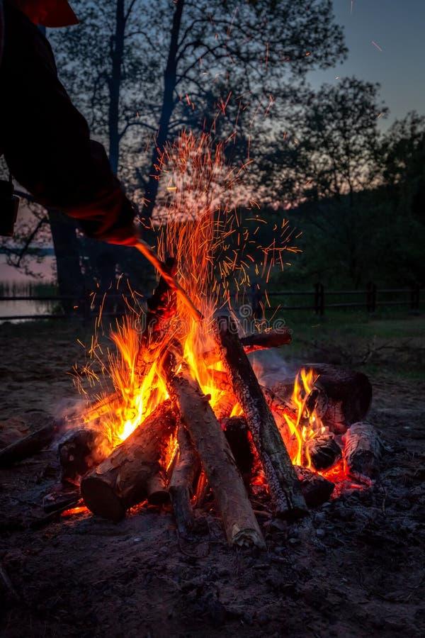 Hoguera hermosa en la oscuridad por el lago en verano foto de archivo