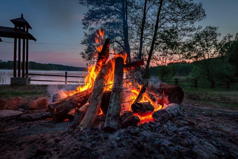 Hoguera maravillosa en la oscuridad por el lago en verano imagen de archivo