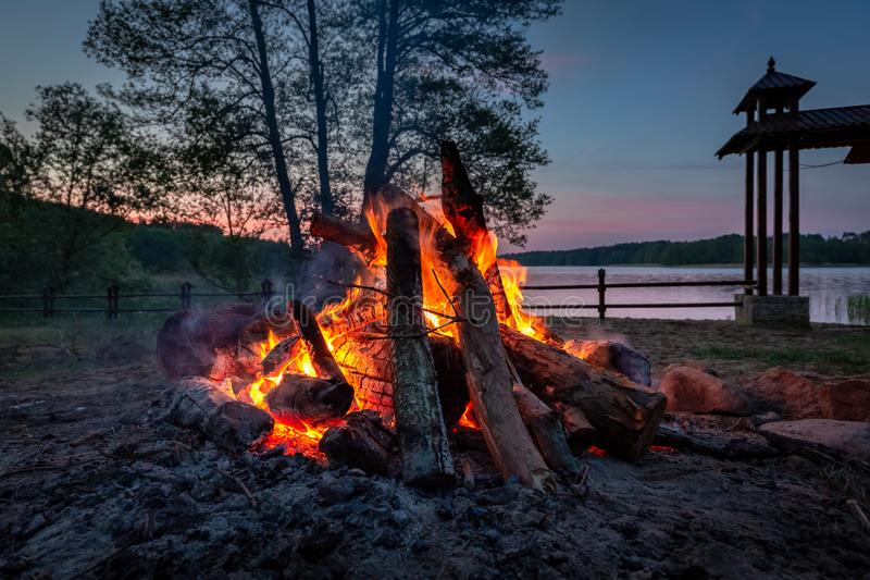 Hoguera maravillosa en la oscuridad por el lago en verano foto de archivo