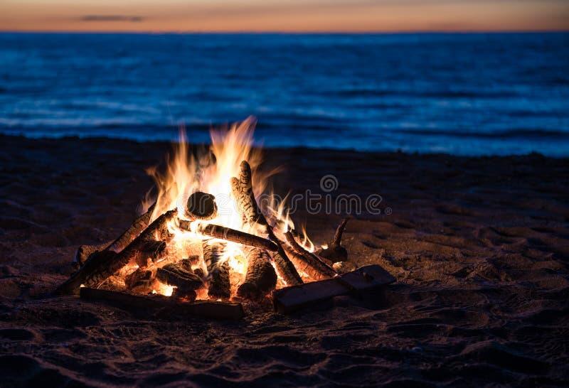 Hoguera por el lago en la puesta del sol imagen de archivo