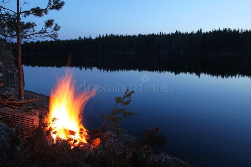 Hoguera por un lago más forrest fotos de archivo