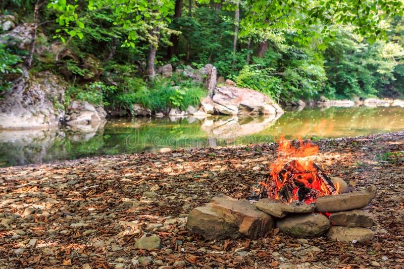 Hoguera que quema en la orilla del río pedregosa en paisaje escénico del día soleado del verano del bosque de la montaña del Cáuc foto de archivo