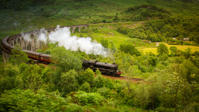 Hogwarts Express steam train from Harry Potter at Glenfinnan Scotland. The Hogwarts Express steam train over the viaduct from the Harry Potter movies at royalty free stock photography