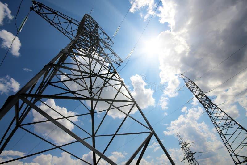 Hohe elektrische Maste gegen Sonne und Himmel lizenzfreies stockbild