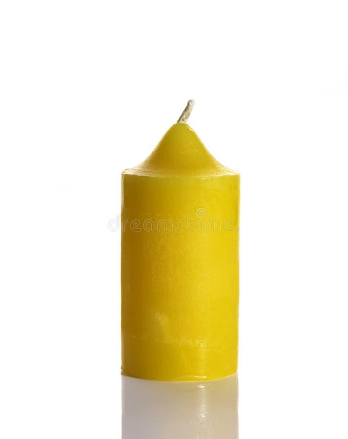 Hohe gelbe Wachskerze auf Weiß stockbild