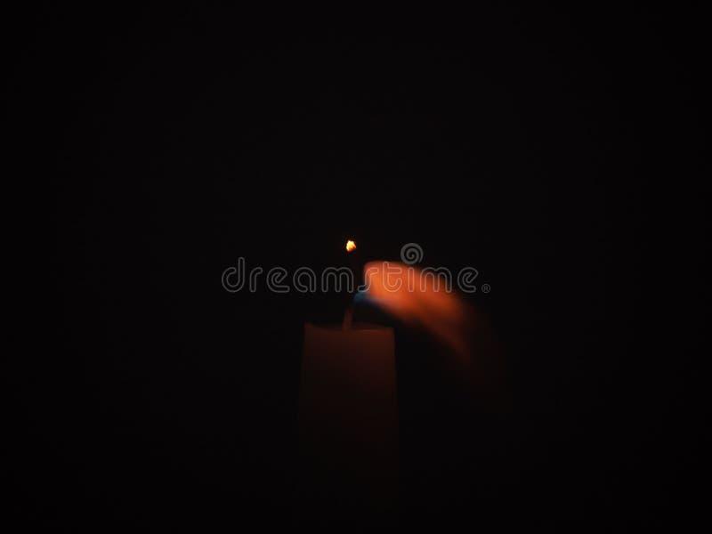 Hohe Kerze durchgebrannt in der dunklen Umwelt stockfotografie