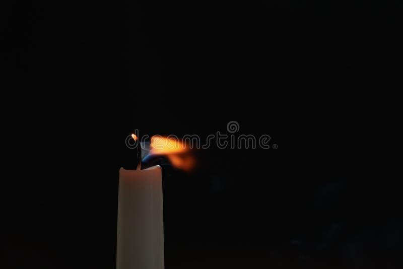 Hohe Kerze weggeblasen in der dunklen Umwelt stockfotos
