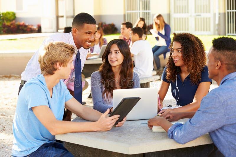 Hohe Schüler, die auf dem Campus mit Lehrer arbeiten lizenzfreies stockbild