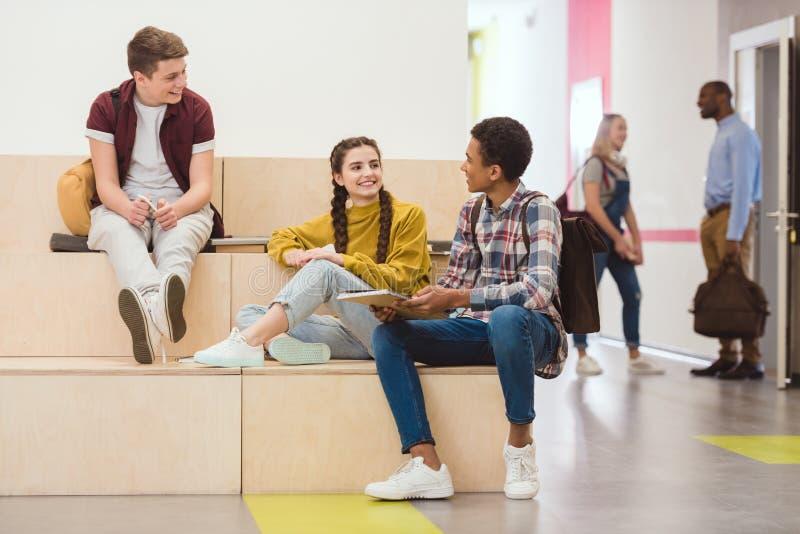 hohe Schüler, die in der Aufenthaltsraumzone sitzen stockfotografie