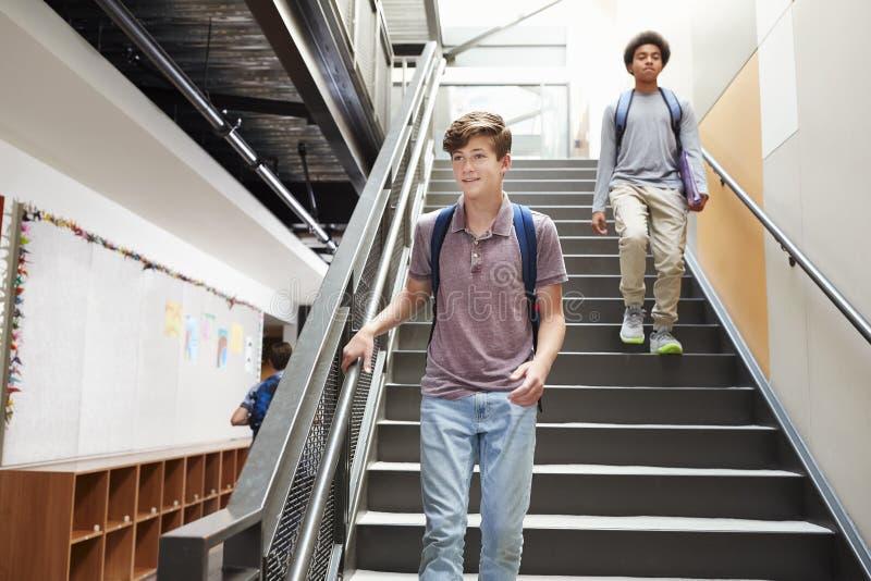 Hohe Schüler, die hinunter Treppe im beschäftigten College-Gebäude gehen lizenzfreie stockfotos
