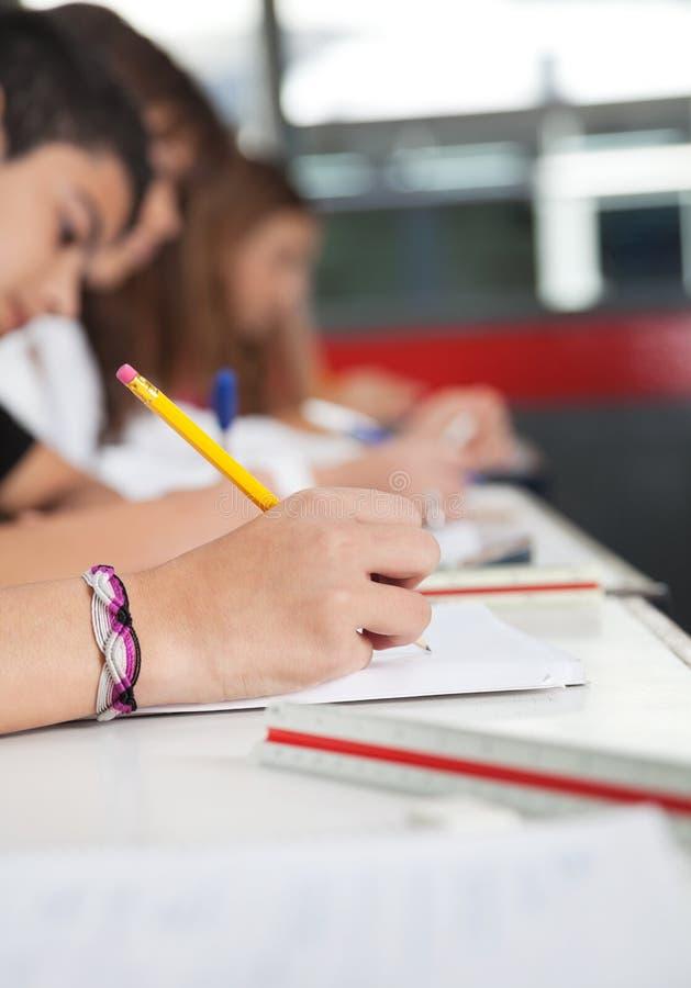 Hohe Schüler, die am Schreibtisch schreiben lizenzfreie stockfotos
