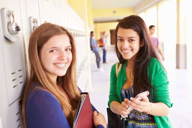 Hohe Schüler durch die Schließfächer, die Handy betrachten stockbilder