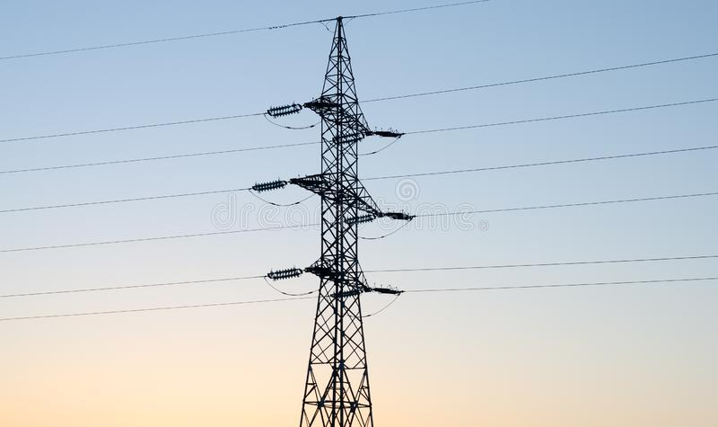 Hohe Winkelsicht der elektrischen Säule gegen orange-blauen Himmel stockbild