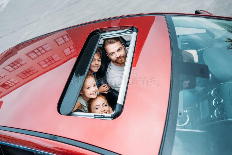 hohe Winkelsicht der Familie schauend aus Schiebedach heraus lizenzfreies stockbild
