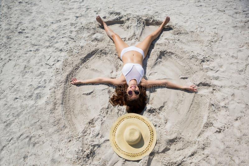 Hohe Winkelsicht der Frau Sandengel am Strand machend stockbild