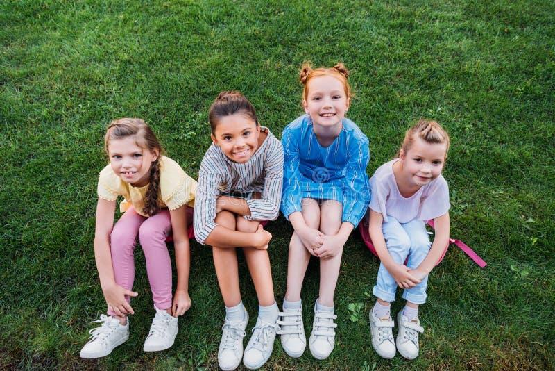 hohe Winkelsicht der Gruppe glücklicher Schulmädchen, die zusammen auf grünem Gras sitzen und Kamera betrachten lizenzfreie stockfotos
