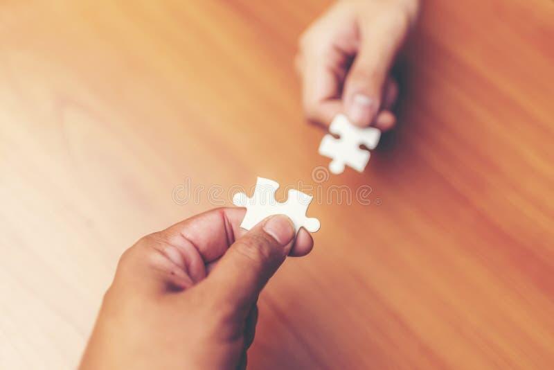 Hohe Winkelsicht der Wirtschaftler-Hand Puzzlen an lösend lizenzfreie stockfotos