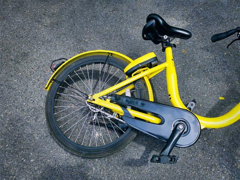 Hohe Winkelsicht des gelben Fahrrades fiel vorbei auf die Straße lizenzfreie stockbilder