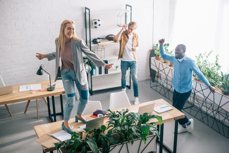 hohe Winkelsicht des glücklichen multiethnischen Geschäftskollegetanzens und haben Spaß in modernem lizenzfreie stockbilder