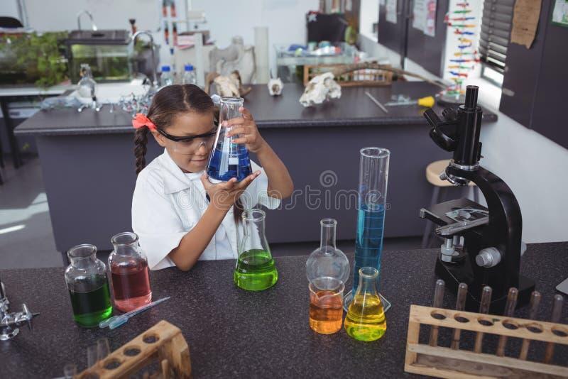 Hohe Winkelsicht des grundlegenden Studenten blaue Chemikalie in der Flasche am Labor überprüfend lizenzfreies stockfoto