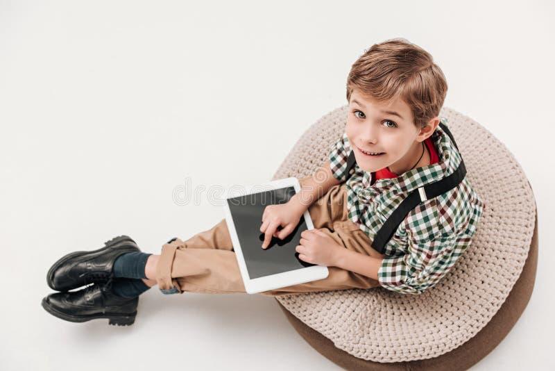 hohe Winkelsicht des kleinen Jungen, der digitale Tablette verwendet und Kamera betrachtet lizenzfreie stockfotos