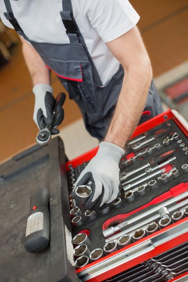 Hohe Winkelsicht des männlichen Mechanikers Werkzeuge im Fach an der AutoReparaturwerkstatt vereinbarend lizenzfreies stockfoto