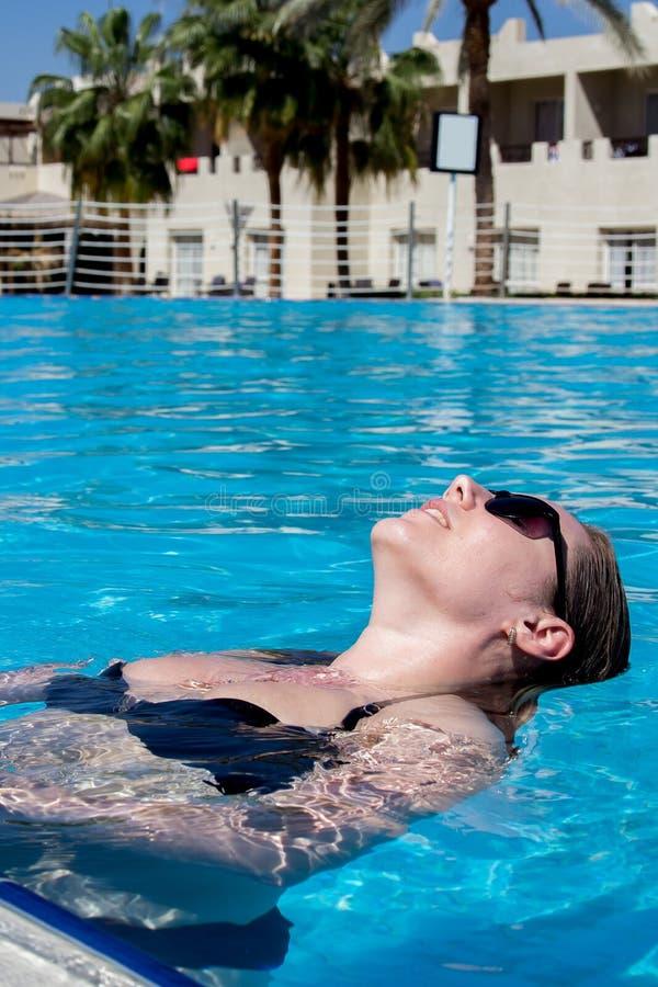 Hohe Winkelsicht des schönen Mädchens in der Sonnenbrille und der Badebekleidung, die im Swimmingpool stillsteht lizenzfreie stockfotos