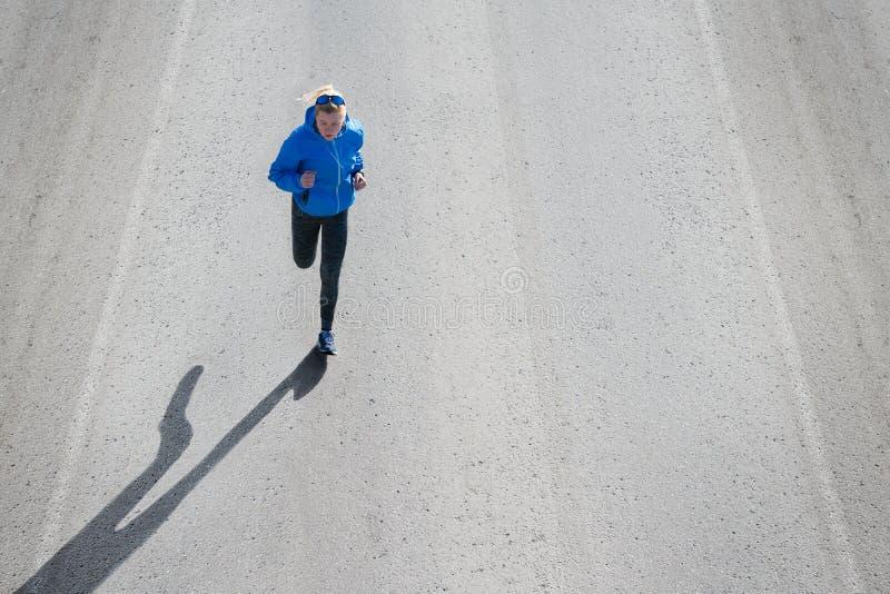 Hohe Winkelsicht des weiblichen Läufers rüttelnd auf Straßenstadt stockbilder