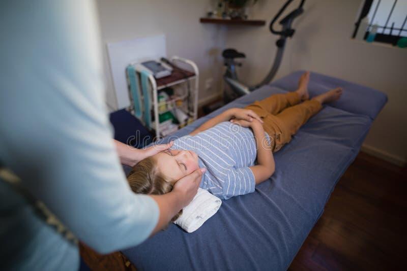 Hohe Winkelsicht des weiblichen Physiotherapeuten Kopfmassage gebend dem Jungen, der auf Bett liegt stockbilder