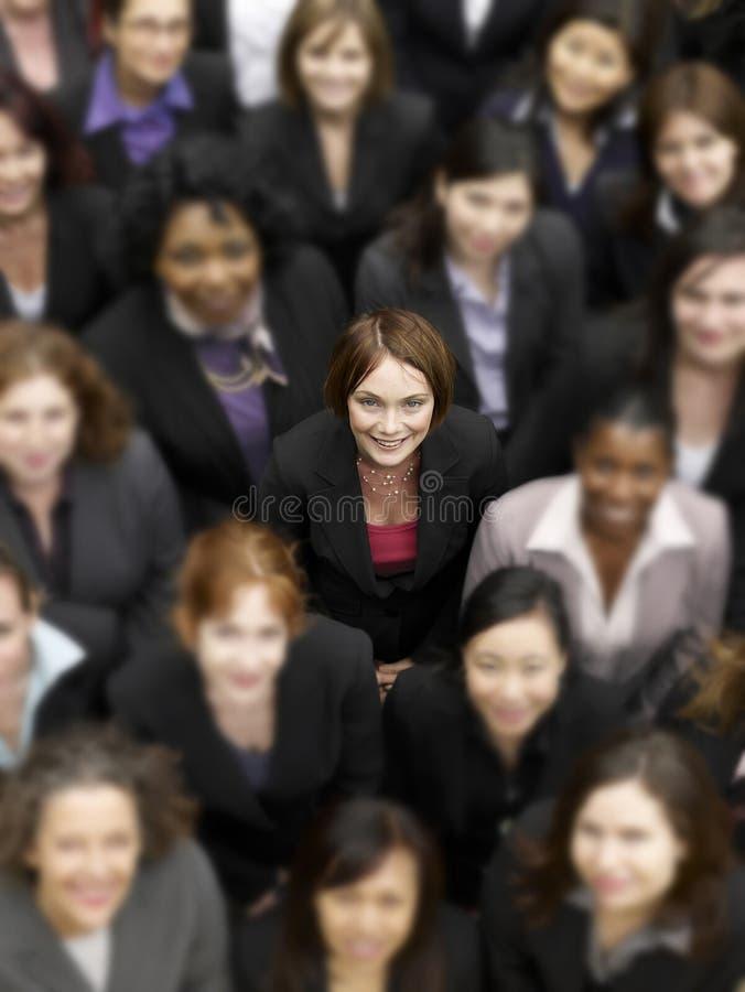 Hohe Winkelsicht einer Geschäftsfrau, die unter multiethnischen Wirtschaftlern steht stockfotos