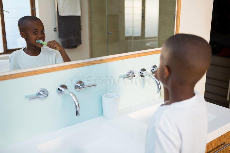 Hohe Winkelsicht von den bürstenden Zähnen des Jungen gesehen von der Spiegelreflexion stockbild