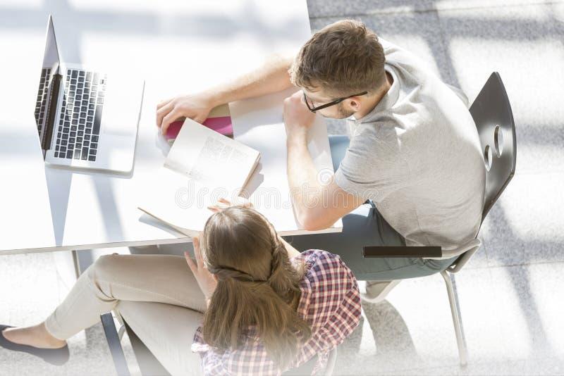 Hohe Winkelsicht von den Studenten, die an Aufgabe an der Bibliothek arbeiten lizenzfreie stockfotografie