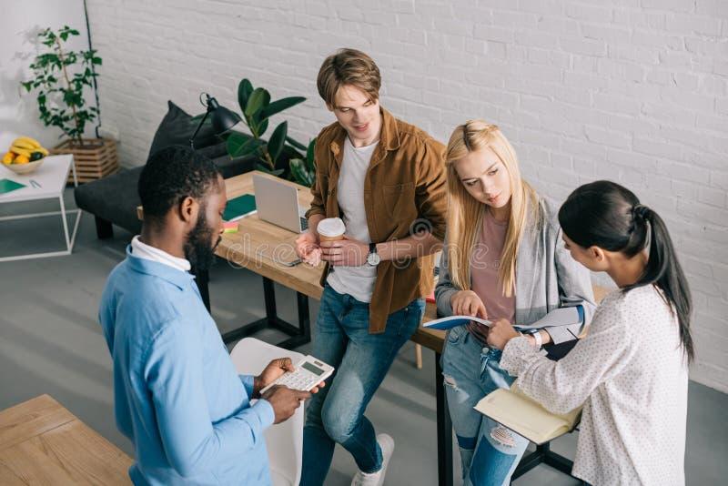 hohe Winkelsicht von multiethnischen Geschäftskollegen mit Lehrbüchern Taschenrechner und Kaffee, die haben lizenzfreie stockbilder