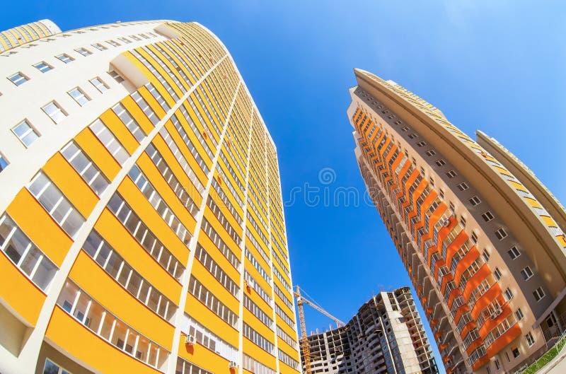 Hohe Wohngebäude im Bau gegen einen blauen Himmel lizenzfreies stockbild