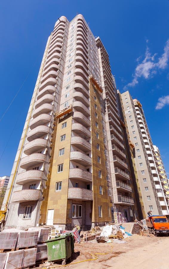 Hohe Wohngebäude im Bau gegen einen blauen Himmel lizenzfreie stockbilder