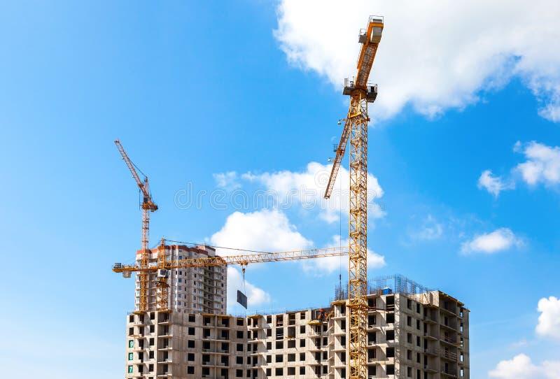 Hohe Wohngebäude im Bau mit Kränen gegen lizenzfreie stockfotografie