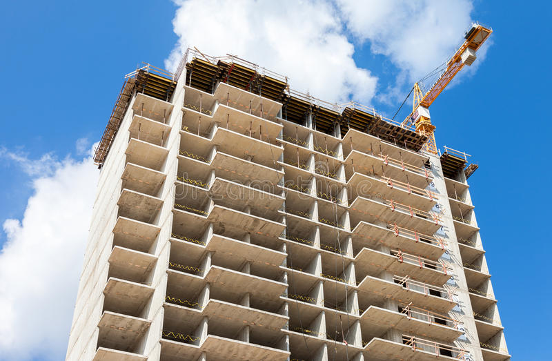 Hohe Wohngebäude im Bau mit Kränen gegen stockfotografie