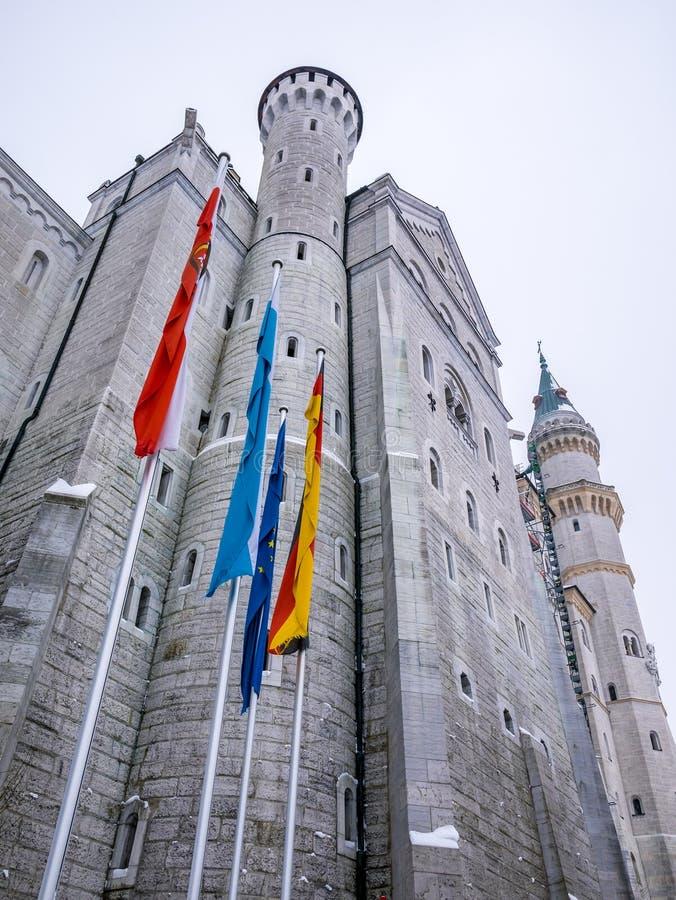 HOHENSCHWANGAU, ALEMANIA - 23 DE FEBRERO DE 2018: Castillo de Neuschwanstein en primer del invierno Bandera de Alemania y de la U imagen de archivo
