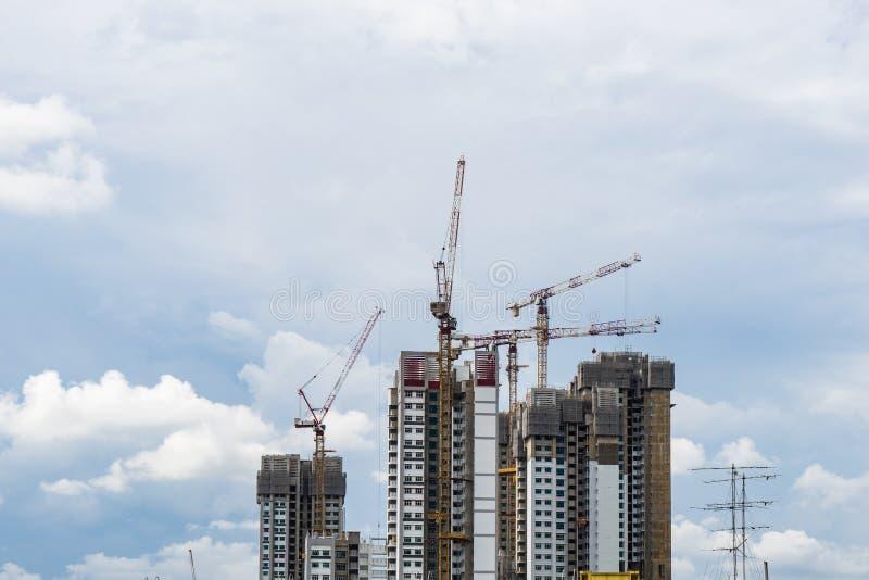 Hoher Aufstiegsturm Singapurs mit dem Kran im Bau stockfotografie