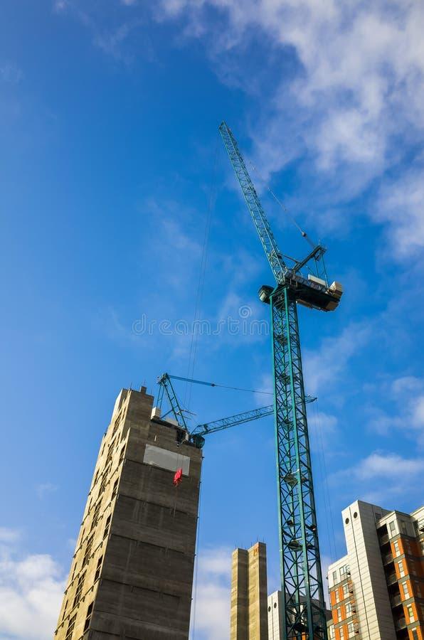 Hoher Kran, der auf einer Baustelle von Wohnungen in einem hohem Gebäude in England, Großbritannien funktioniert lizenzfreie stockfotos