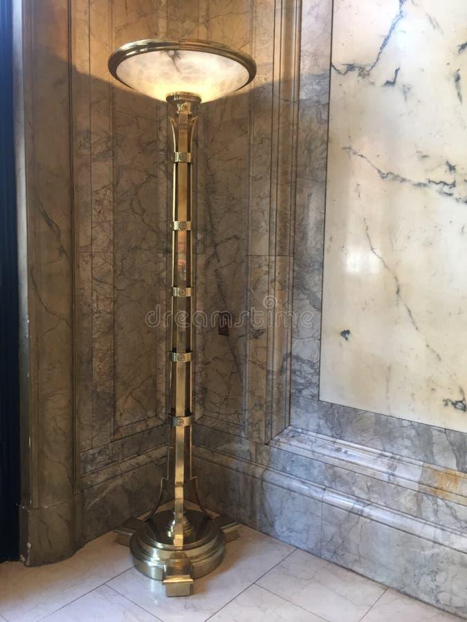 Hoher Messingbeleuchtungsstand mit Marmorwand und Boden stockfoto