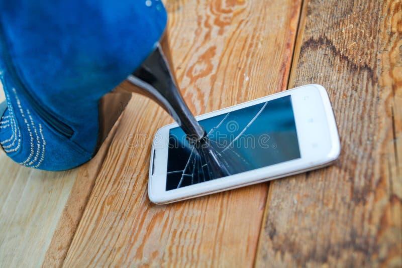 Hoher Schuh, der einen Handy zerquetscht lizenzfreies stockbild